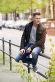Junger blonder Mann, der draußen sitzt Stockfoto