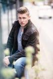 Junger blonder Mann, der draußen sitzt Stockbilder