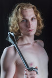 Junger blonder Mann, der eine mittelalterliche Waffe hält Stockfotografie