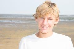Junger blonder Mann, der im sonniger Tagesstrand lächelt Stockfoto