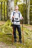 Junger blonder Mann, der im Wald steht lizenzfreie stockbilder