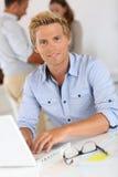 Junger blonder Mann, der mit Laptop arbeitet Lizenzfreies Stockbild
