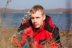 Junger blonder Mann in der roten Jacke sitzen auf der Küste. Stockfotos