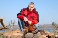 Junger blonder Mann in der roten Jacke sitzen nahe Feuer. Stockfotografie