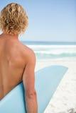 Junger blonder Mann, der sein blaues Surfbrett anhält Stockbild