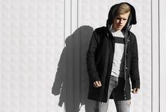 Junger blonder Mann im Herbst kleidet stehende nahe weiße Wand Lizenzfreie Stockfotografie