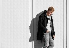 Junger blonder Mann im Herbst kleidet stehende nahe weiße Wand Lizenzfreies Stockbild