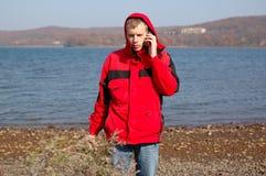 Junger blonder Mann im roten Jackengespräch auf Handy Stockfotos