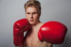 Junger blonder Mann mit Boxhandschuhen Stockbilder