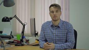 Junger blonder Mann mit einem Bart und einem karierten Hemd, die an seinem Schreibtisch im Büro sitzen stock video