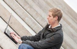 Junger blonder Mann mit Laptop Stockfotografie