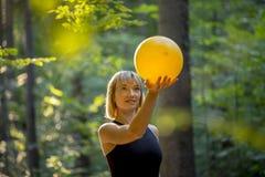 Junger blonder pilates Auszubildender, der einen gelben Ball hält Stockfoto