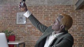 Junger blonder stilvoller afrikanischer Geschäftsmann, der selfie nimmt und im modernen Büro, modischer Mann mit dem durchbohrten stock video footage
