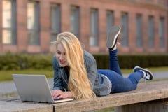 Junger blonder Student, der auf einer Bank liegt und an ihrem Laptop arbeitet Stockfotografie
