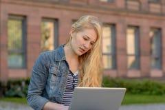 Junger blonder Student, der auf einer Bank sitzt und an ihrem Laptop arbeitet Stockfotografie