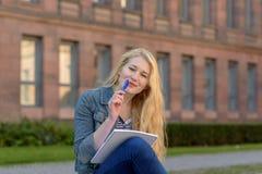 Junger blonder Student, der auf einer Bank sitzt und Kenntnisse nimmt Lizenzfreie Stockbilder