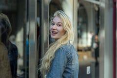 Junger blonder Student steigt in eine Tram ein Stockbild