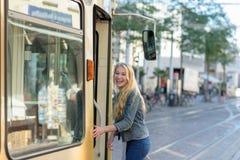 Junger blonder Student steigt in eine Tram ein Stockfotos