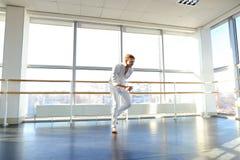 Junger blonder Tänzer genießt, in der weißen Klage zu gewinnen und macht warm Lizenzfreie Stockbilder
