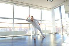 Junger blonder Tänzer genießt, in der weißen Klage zu gewinnen und macht warm Lizenzfreie Stockfotos