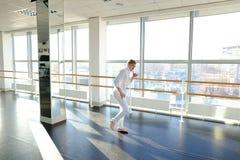 Junger blonder Tänzer genießt, in der weißen Klage zu gewinnen und macht warm Stockfotografie