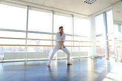 Junger blonder Tänzer genießt, in der weißen Klage zu gewinnen und macht warm Lizenzfreies Stockfoto