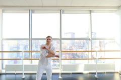Junger blonder Tänzer genießt, in der weißen Klage zu gewinnen und macht warm Lizenzfreie Stockfotografie
