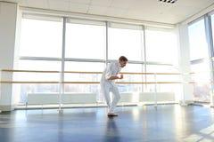 Junger blonder Tänzer genießt, in der weißen Klage zu gewinnen und macht warm Stockbild