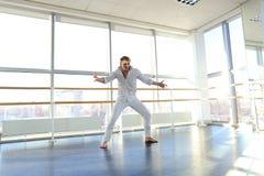 Junger blonder Tänzer genießt, in der weißen Klage zu gewinnen und macht warm Stockbilder