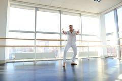Junger blonder Tänzer genießt, in der weißen Klage zu gewinnen und macht warm Lizenzfreies Stockbild
