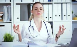 Junger blonder weiblicher Arzt, der Yoga tut und mit Augen sich entspannt, schloss am Arbeitsplatz Kurze Pause in der harten Arbe Lizenzfreies Stockbild