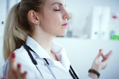 Junger blonder weiblicher Arzt, der Yoga tut und mit Augen sich entspannt, schloss am Arbeitsplatz Kurze Pause in der harten Arbe Stockbild