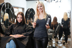 Junger blonder weiblicher Friseur, der Scheren und Kamm hält Lizenzfreie Stockfotos