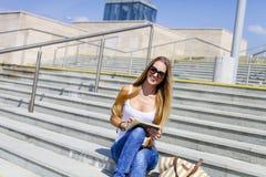 Junger blonder weiblicher Student, der den Tablet-Computer im Freien verwendet Stockfotos