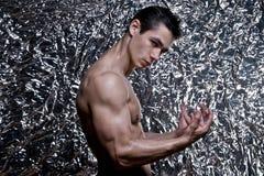 Junger Bodybuilder, der Muskeln biegt Stockfoto