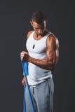 Junger Bodybuilder, der sein Bizeps bearbeitet stockfoto