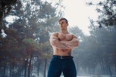 Junger Bodybuilder mit dem bloßen Torso steht mit den Armen, die im nebelhaften Wald des Winters gekreuzt werden stockfoto