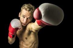 Junger Boxer, der einen Durchschlag durchführt Lizenzfreie Stockfotografie