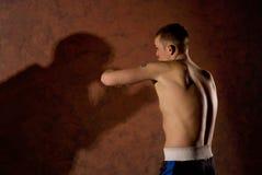 Junger Boxer, der einen schattenhaften Gegner kämpft Stockfotografie