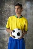 Junger brasilianischer Fußball-Spieler in der Uniform hält Fußball Lizenzfreies Stockfoto