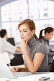 Junger Büroangestellter, der den Laptop sitzt am Schreibtisch verwendet Stockfoto