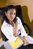 Junger Büroangestellter, der mit dem Notizbuch betriebsbereit zu sitzt Lizenzfreies Stockfoto