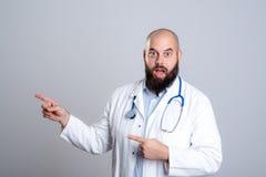 Junger bärtiger Doktor, der überrascht schaut und auf Seite zeigt Stockfotografie