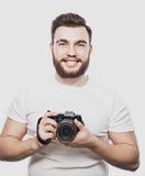 Junger bärtiger Fotograf, der Fotos mit Digitalkamera macht Stockbilder