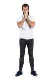 Junger bärtiger Hippie, der sein Gesicht mit den Händen niest und bedeckt Stockfoto