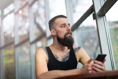 Junger bärtiger Mann, der Handy verwendet Stockbild