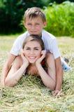 Junger Bruder und ältere Schwester oder Mutter u. Sohn, die zusammen auf trockenem Heu am Sommertag lächeln Stockbild