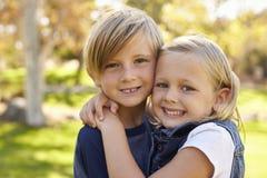 Junger Bruder und die Schwester, die in einem Park umfasst, schauen zur Kamera Lizenzfreies Stockbild
