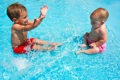 Junger Bruder und Schwester, die im Pool spielt Lizenzfreie Stockfotos