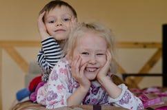 Junger Bruder und Schwester, die zusammen auf einem Bett liegt Lizenzfreies Stockbild